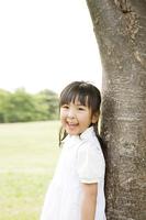 木に寄りかかる笑顔の女の子
