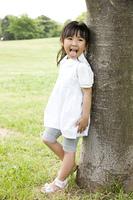木に寄り掛かって遊ぶ女の子