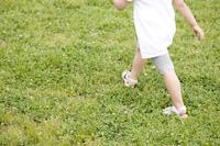 芝生の上を歩く女の子の足元