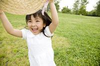 麦藁帽子で遊ぶ女の子