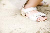 砂遊びをする女の子の足元