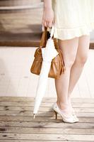 日傘と鞄を持った女性の足元
