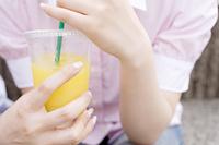 オレンジジュースを持つ女性の手元