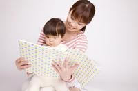 母親に本を読んでもらっている赤ちゃん