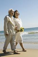 Senior Newlyweds Walking Along Beach
