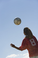Teenage Girl Heading Soccer Ball