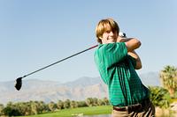 Young Man Swinging Golf Club