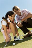 Golfer and Instructor Eyeing Putt