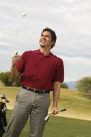 Golfer Holding Putter Tossing Golf Ball in Air