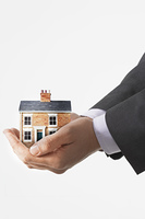 Person holding small house in cupped hands