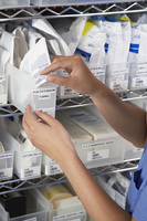 Nurse at shelves with medical supply  close-up of hands