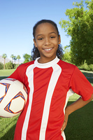 Girl (7-9 years) soccer player holding ball under arm  portrait