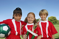 Three children (7-9 years) holding soccer ball and trophy on soccer field  portrait