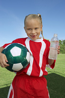 Girl (7-9 years) soccer player holding ball and water bottle  portrait