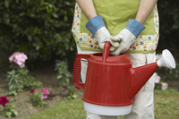 Woman holding watering can in garden  mid section