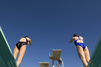 Two female swimmers standing on diving board