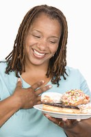 Mid-adult overweight  woman holding plate with donuts and smiling