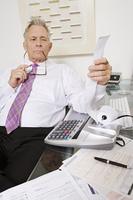 Businessman Looking at Calculator Paper