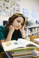 High School Student Reading in Library