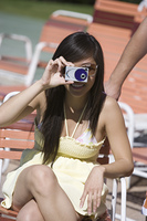Young woman using camera outdoors