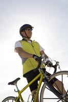 Senior man with bike, low angle view