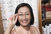Woman trying on eyeglasses in store