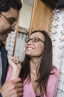 Couple trying on eyeglasses in store