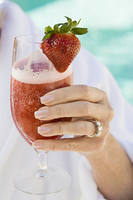 Senior woman holding strawberry cocktail, close-up