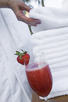 Senior woman holding towel near strawberry cocktail, close-up