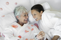 Mother and daughter with mobile phone on bed