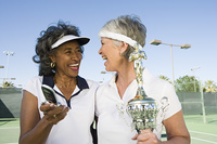 Two female tennis players with award cup