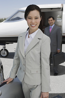 Portrait of mid-adult businesswoman standing in front of convertible, mid-adult businessman in background.
