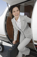 Asian businesswoman getting off private airplane.
