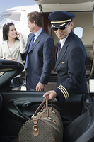 Mid-adult businesswoman and businessman standing in front of private jet, while pilot holding their luggage.