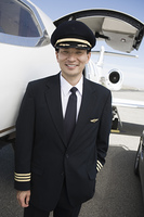 Asian male pilot in front of airplane, elevated view.
