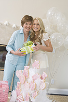 Bride and her Friend standing Together holding gift at Bridal Shower