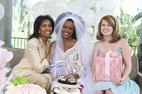 Bride holding gifts with friends at bridal shower