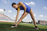 Female athlete stretching, portrait
