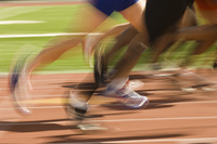 Low section of runners running on a track