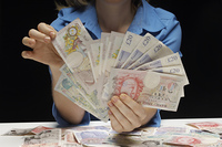 Woman holding fan of banknotes