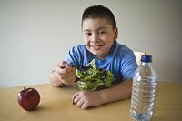 Pre-teen (10-12) boy sitting at desk and eating salad