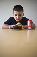 Pre-teen (10-12) boy sitting at desk and looking at dessert