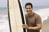 Portrait of man holding surfboard on beach