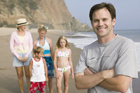 Portrait of man on beach with family
