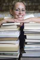 Portrait of female librarian with stacked books