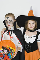 Portrait of girl embracing boy (7-9), wearing Halloween costumes