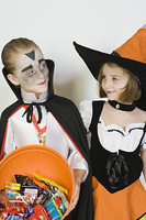 Girl and boy (7-9), wearing Halloween costumes, studio shot