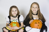 Portrait of girls (7-9) wearing Halloween costumes, with jack-o-lanterns