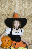 Portrait of girl (7-9) wearing witch costume by hay