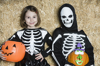 Portrait of girls (7-9) wearing skeleton costumes, with jack-o-lanterns